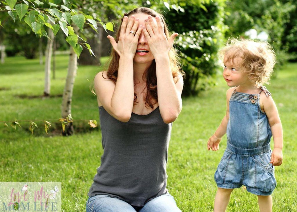 mom and toddler playing hide and seek game outside