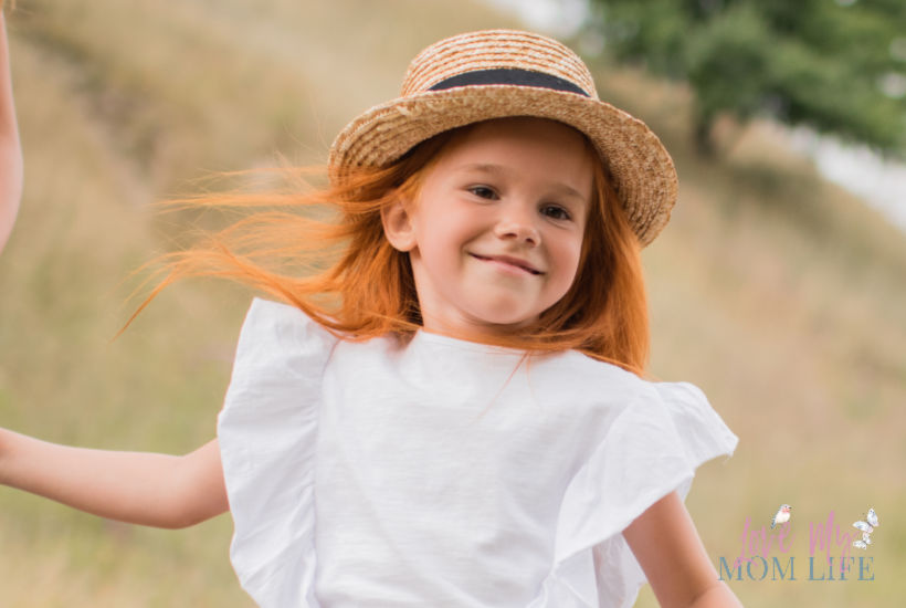 Cute red-headed girl with straw hat  and white dress on in field.
